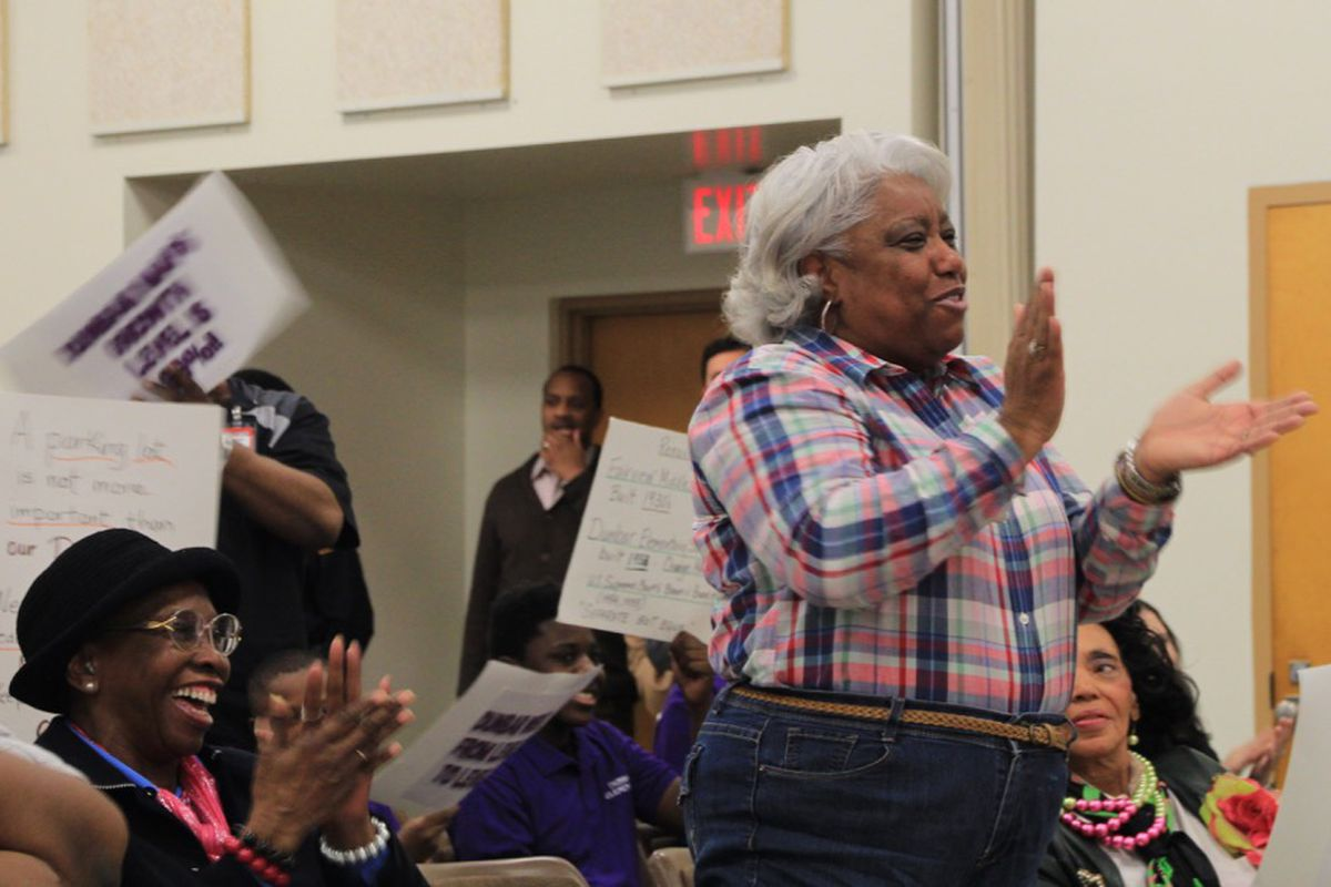 Claudette Boyd applauds during public comment at a Shelby County Schools board meeting regarding a vote to close Dunbar Elementary School.