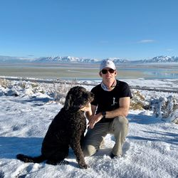 Jason Steed and Pepper, his 5-year-old labradoodle, rest on Antelope Island's east trail in the snow.