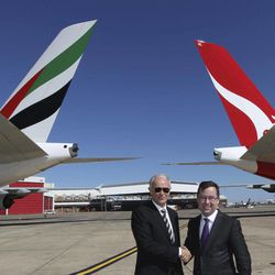 Qantas CEO Alan Joyce, right, and Emirates President Tim Clark pose for photos in front of their respective aircraft  after announcing a global aviation partnership in Sydney, Australia, Thursday, Sept. 6, 2012. Qantas Airways Ltd. announced Thursday that it has signed a 10-year partnership deal with rival Emirates in a bid to boost the Australian airline's struggling international division. The deal is subject to regulatory approval.