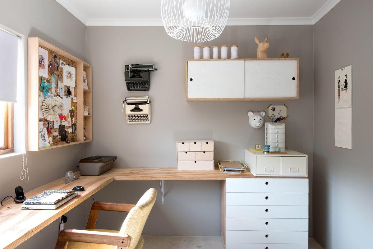 A gray office with a natural wood corner desk and white accents.
