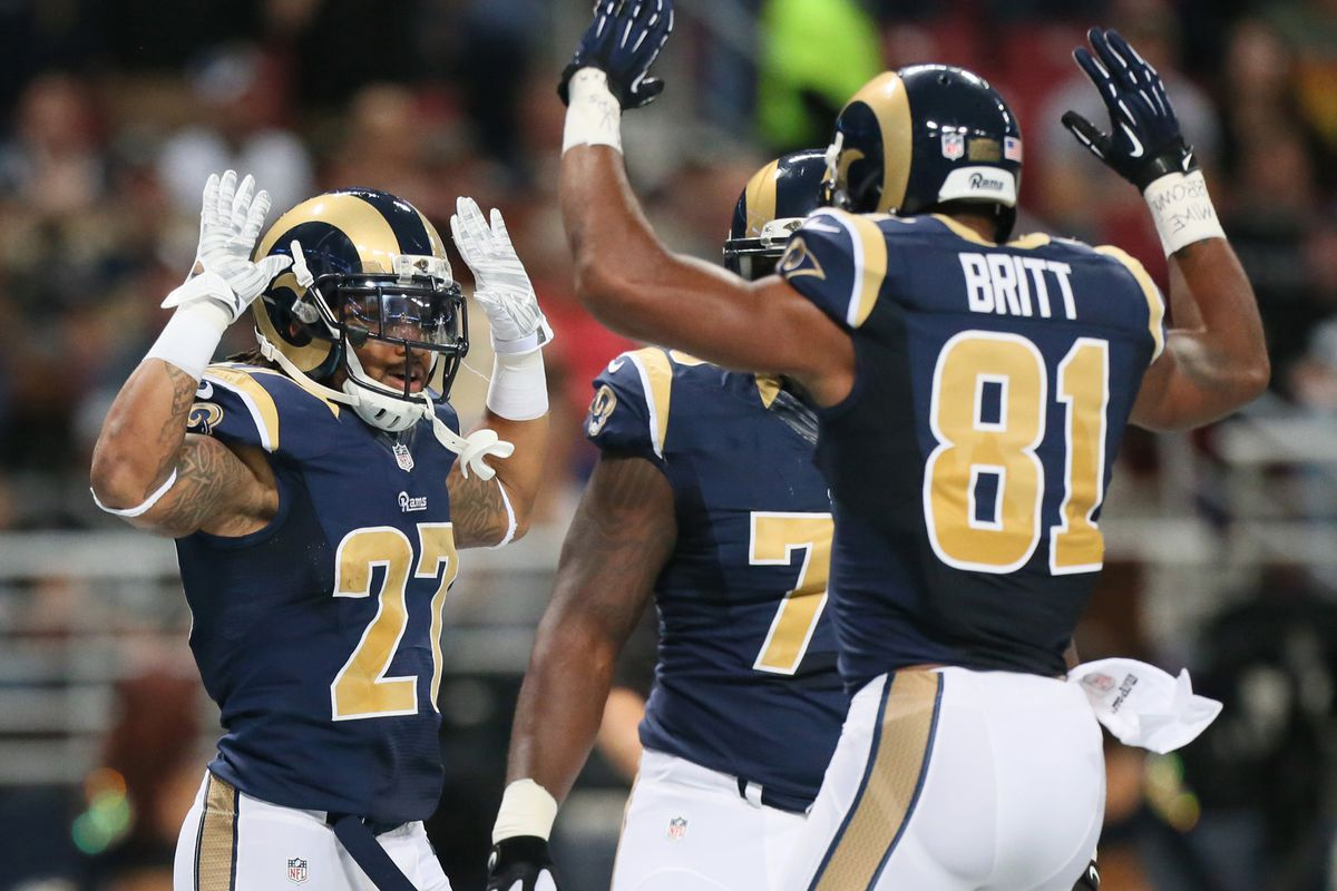 """St. Louis Rams players make a """"hands up, don't shoot"""" gesture."""