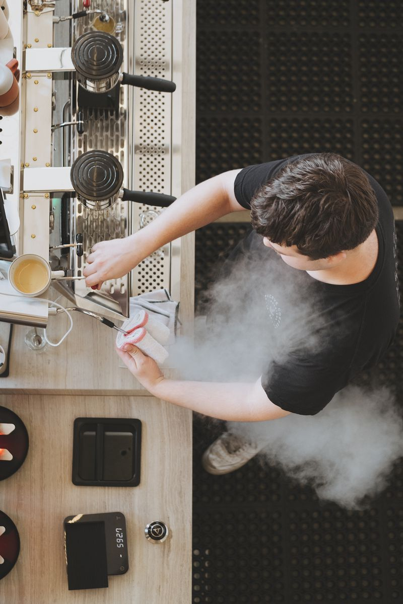 A barista letting steam off a machine from above.
