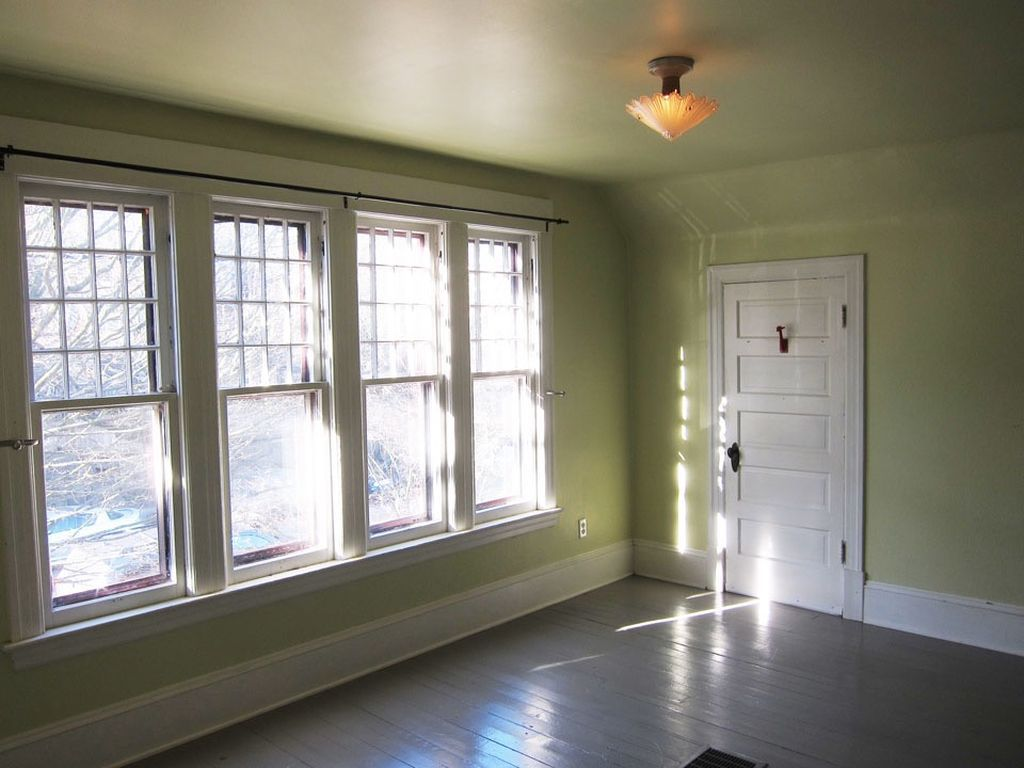 A green room with white trim and moulding, and four windows on the left wall