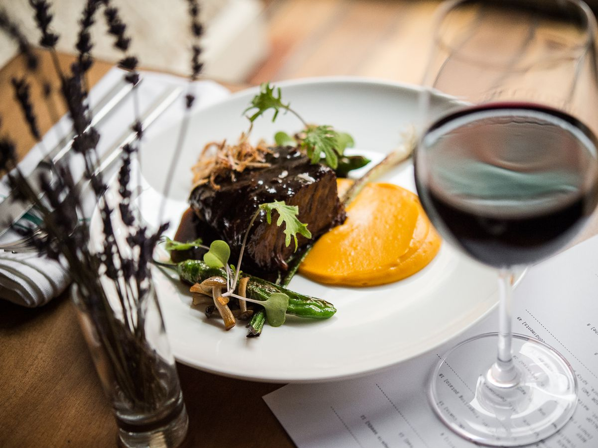 A glass of red wine and flowers in front of a white plate with a saucy meat dish at Tuome.