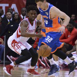 The Shanghai Sharks Jimmer Fredette (32) battles for the ball against the Houston Rockets Isaiah Taylor (17) in the second half of an NBA basketball exhibition game Sunday, Oct. 2, 2016, in Houston.