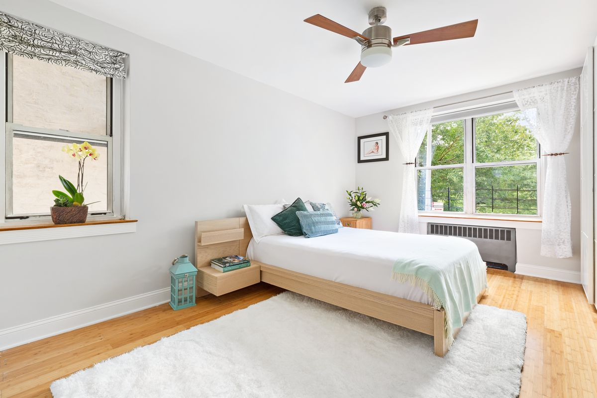 A bedroom with a white rug, a small bed, a large window, and white walls.
