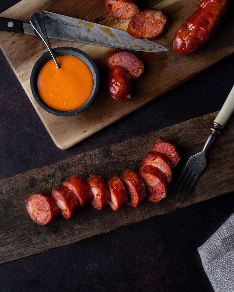 A sliced up sausage with an orange sauce placed on a wooden cutting board