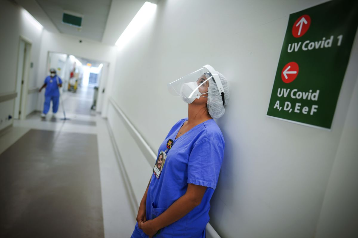 In this March 19, 2021 file photo, a health worker pauses in the ICU unit for COVID-19 patients at the Hospital das Clinicas in Porto Alegre, Brazil. As Brazil hurtles toward an official COVID-19 death toll of 500,000 — second-highest in the world — science is on trial inside the country and the truth is up for grabs.