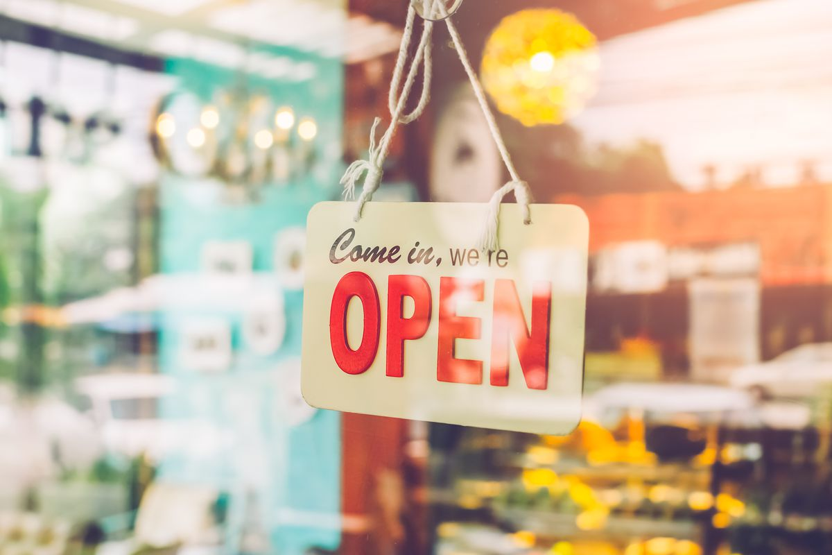 """A sign in the window of a cafe says """"Come in, we're open"""" with the background blurry"""