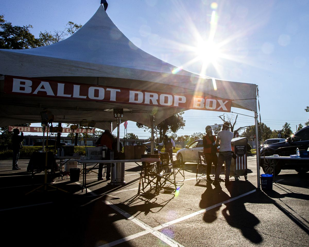 """A white tent with open sides — it has a red and white banner reading """"Ballot Drop Box."""" Underneath it are tables and volunteers; beneath a bright sun is a line of cars, coming to drop ballots off."""