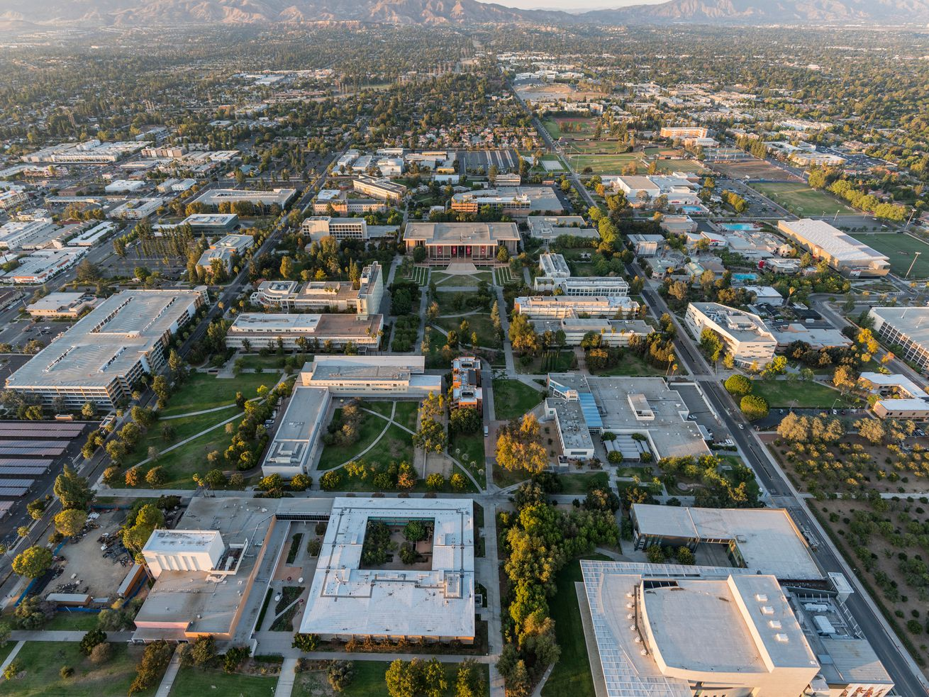 An aerial view of a college campus, surrounded by a grid of streets with low-slung buildings