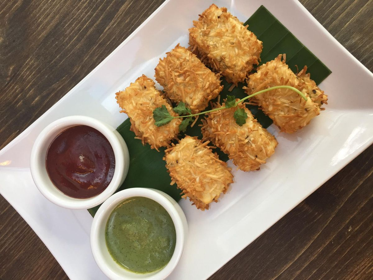 A top-down view of coconut fried fritters, with a green sauce and a red sauce on the side.