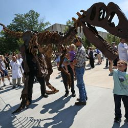 Kayson Weyburn reaches for Tim Seeber's Mr. Bones Allosaurus costume at the ribbon-cutting ceremony for the new Tracy Hall Science Center at Weber State University in Ogden on Wednesday, Aug. 24, 2016.