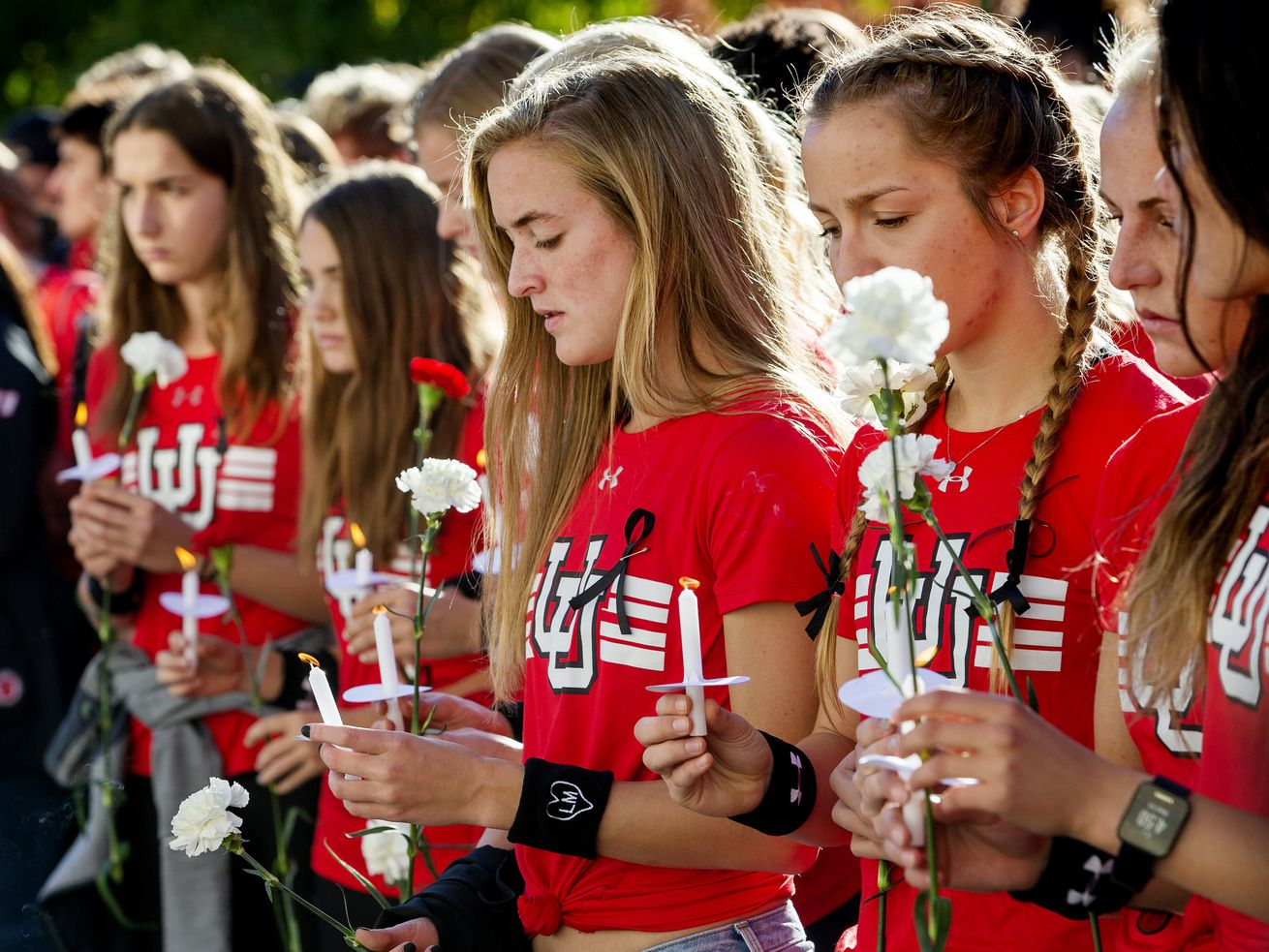 Members of the University of Utah track team attend a vigil for Lauren McCluskey at the Park Building on Wednesday, Oct. 24, 2018. McCluskey was killed by a man blackmailing her over intimate photos, which were then shared by a police officer investigating the case. Utah lawmakers voted to close a loophole that prevented charges against the police officer.