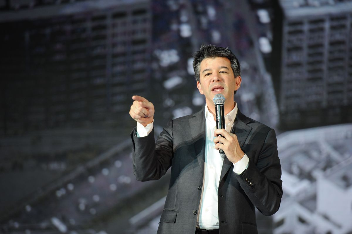 Former Uber CEO Travis Kalanick onstage holding a microphone and pointing at the audience
