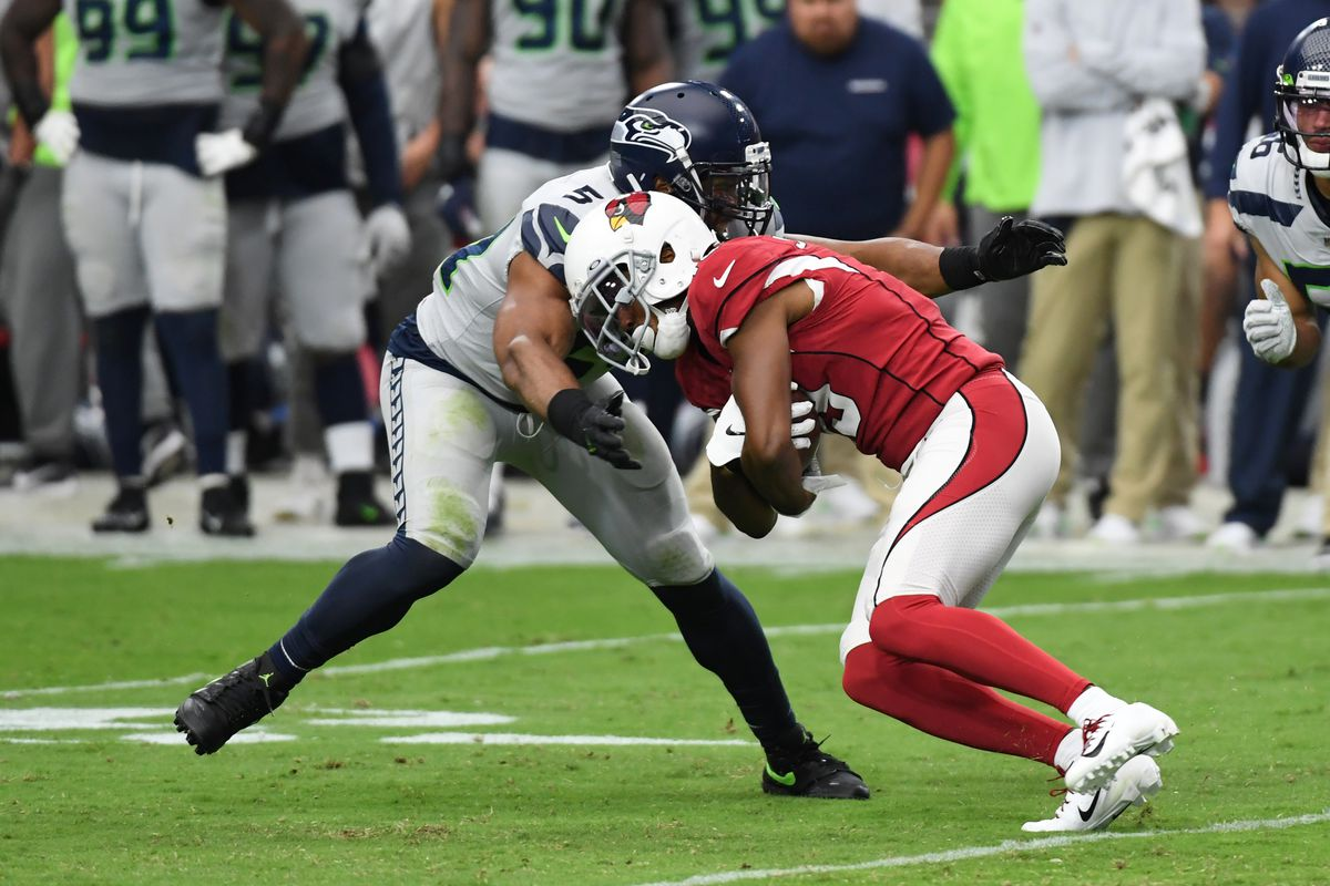 Christian Kirk of the Arizona Cardinals runs with the ball while attempting to avoid a tackle by Bobby Wagner of the Seattle Seahawks during the second half at State Farm Stadium on September 29, 2019 in Glendale, Arizona.