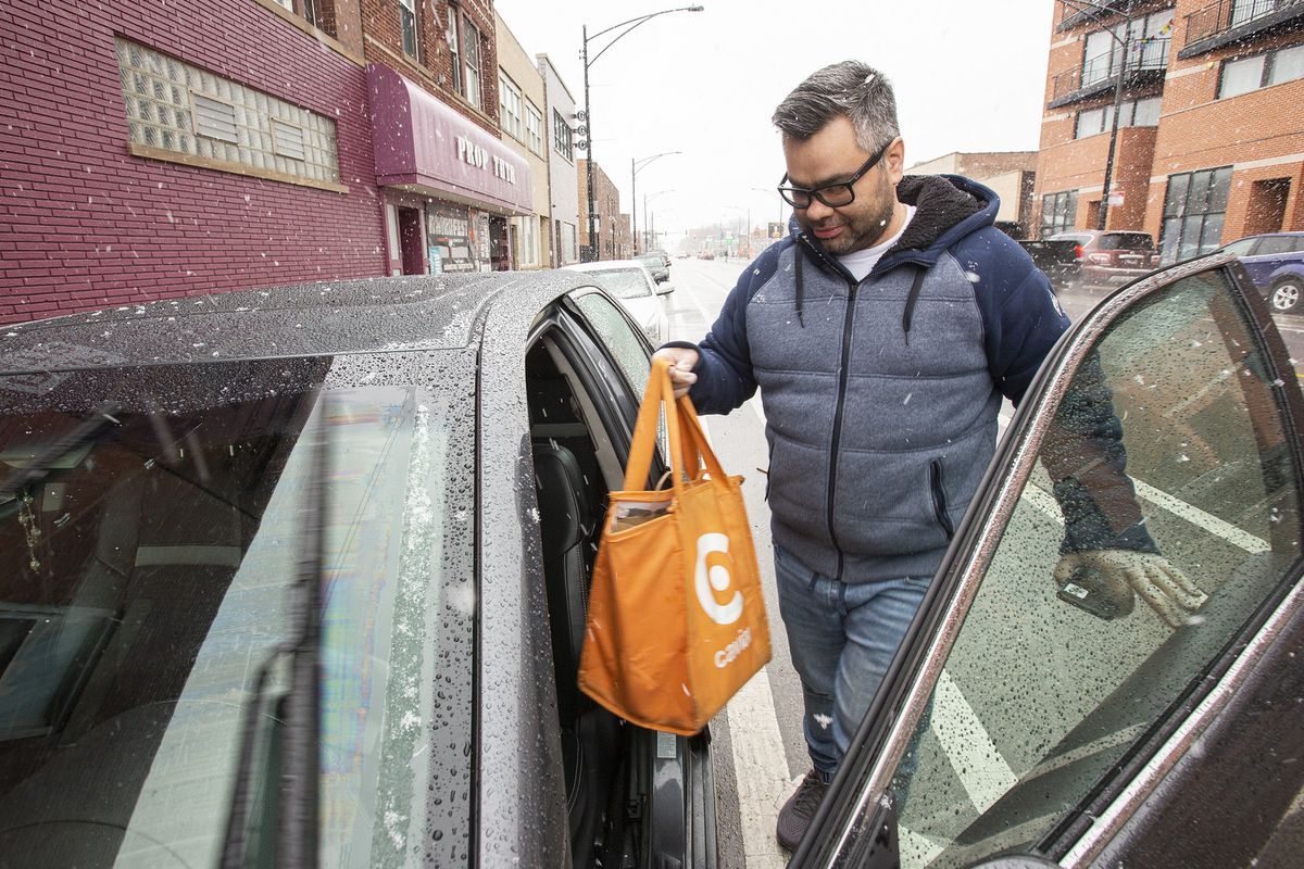 A courier with an orange bag bringing a food delivery into a car.