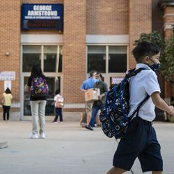 Parents and students arrive Monday at George Armstrong Elementary School in Rogers Park for the first day of school for Chicago Public Schools.