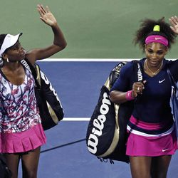 Venus Williams, left, and Serena Williams wave as they walk off the court following their 6-1, 6-4 loss to Russia's Maria Kirilenko and Nadia Petrova in their match during the third round of women's doubles play at the U.S. Open tennis tournament, Monday, Sept. 3, 2012, in New York.