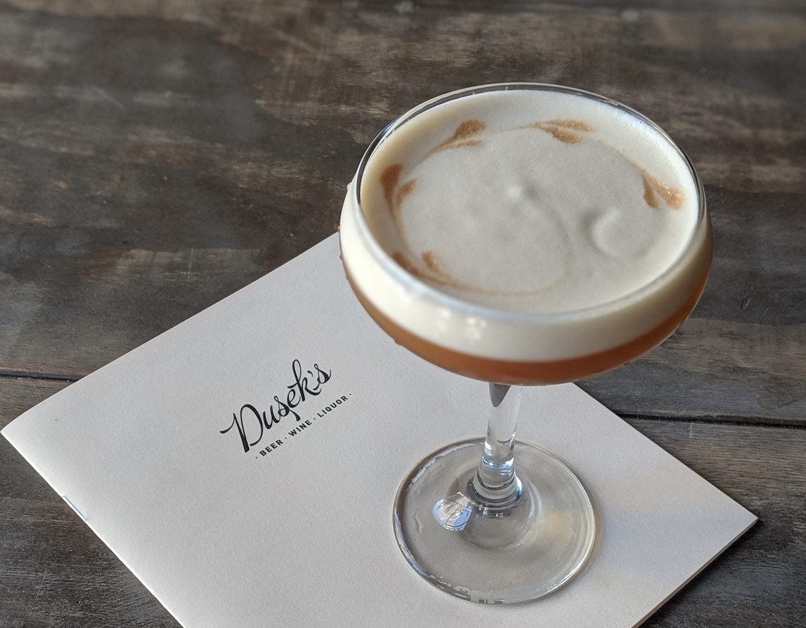 A coupe glass positioned on top of a menu, holding a brown-colored drink topped with egg white foam.