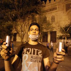 An Egyptian protester holds tear gas canisters fired during clashes between Egyptian police and protesters in front of the U.S. embassy in Cairo, Egypt ,Thursday, Sept. 13, 2012, as part of widespread anger across the Muslim world about a film ridiculing Islam's Prophet Muhammad.