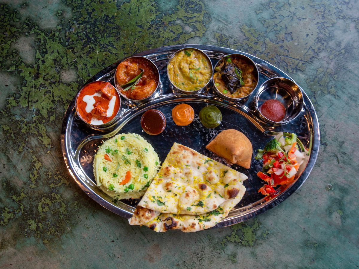 A thali with naan, rice, and a variety of small bowls filled with sauces and vegetables.