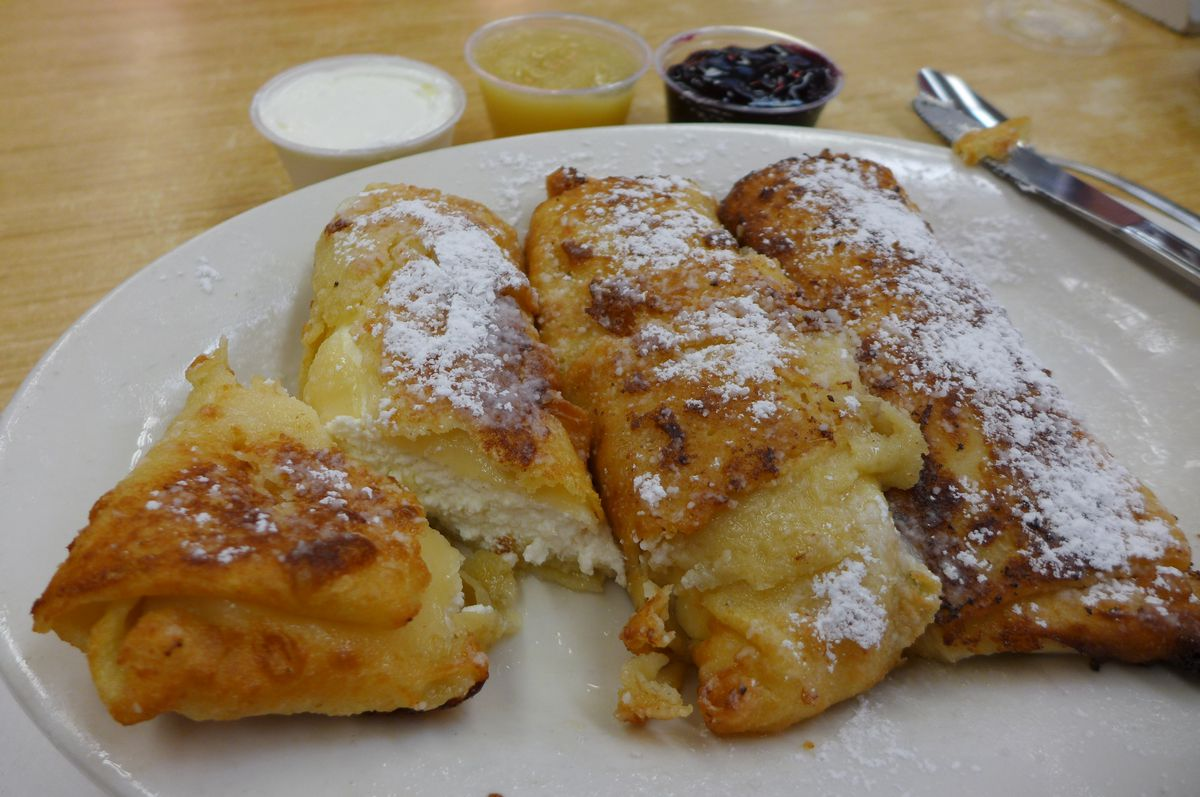 Cheese blintzes covered with powdered sugar, three to a plate.