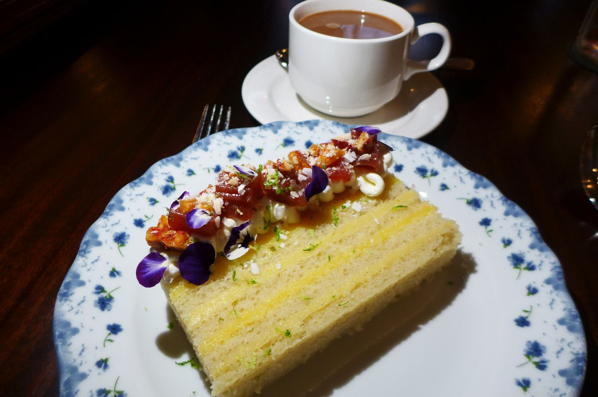 A slice of white cake laying flat with a cup of coffee in the background.