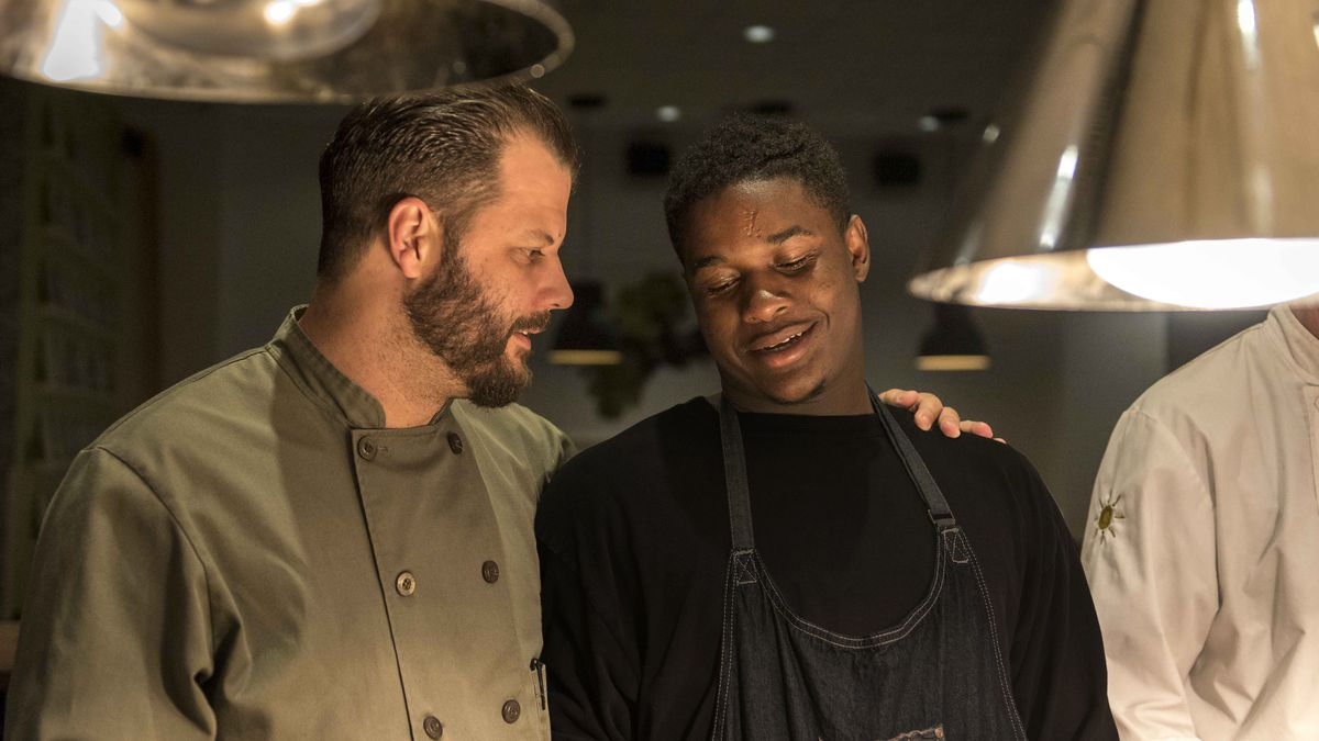 Chef Chad Houser, left, stands with an intern in the kitchen at Cafe Momentum