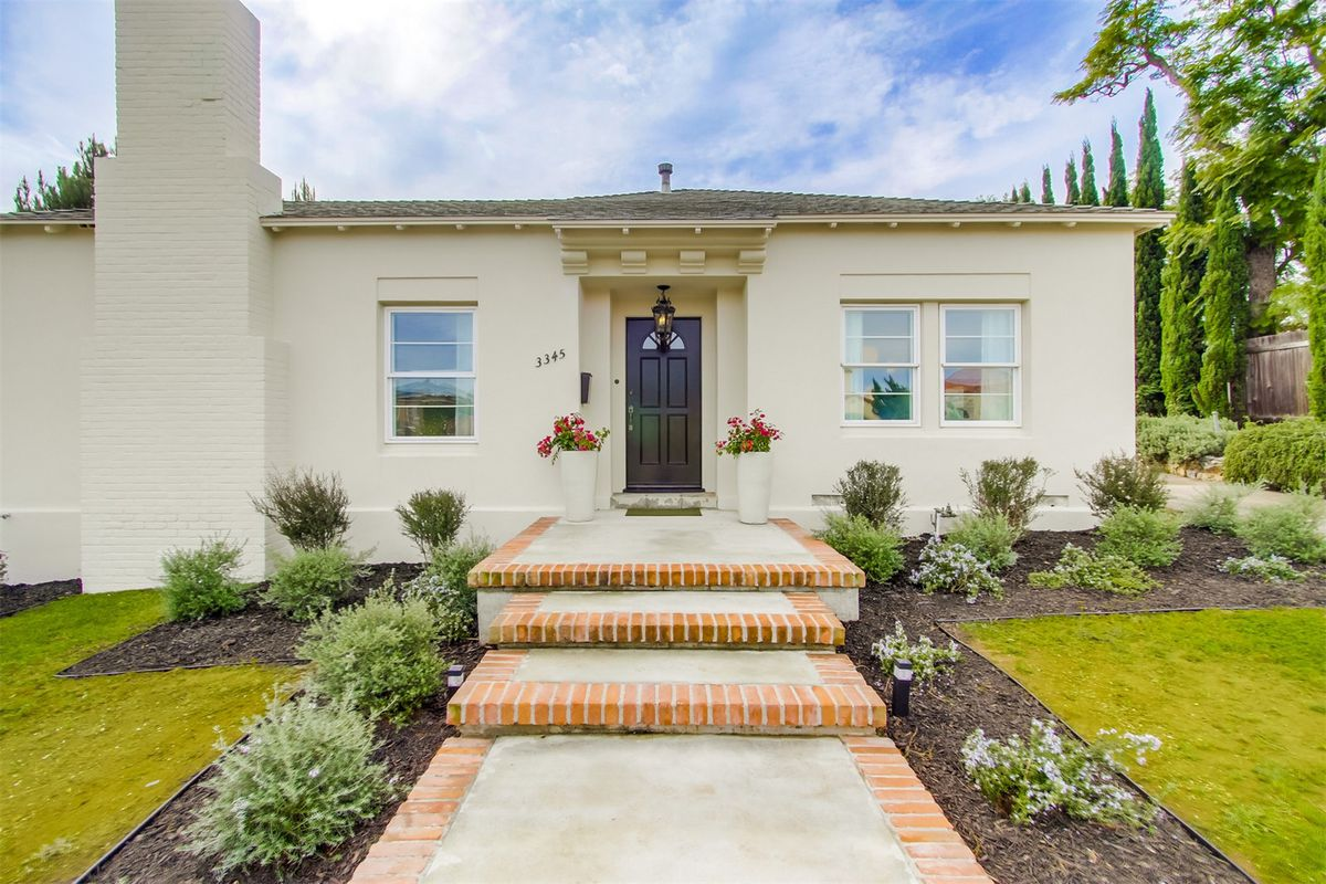 Single-story stucco bungalow with stepped walkway and landscaped front yard.