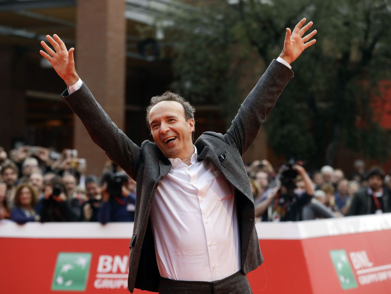 In this 2016 file photo, actor Roberto Benigni poses for photographers as he arrives on the red carpet at the Rome Film Festival.
