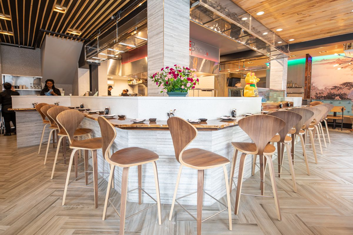 counter seating at a restaurant with white counter and light wood chairs