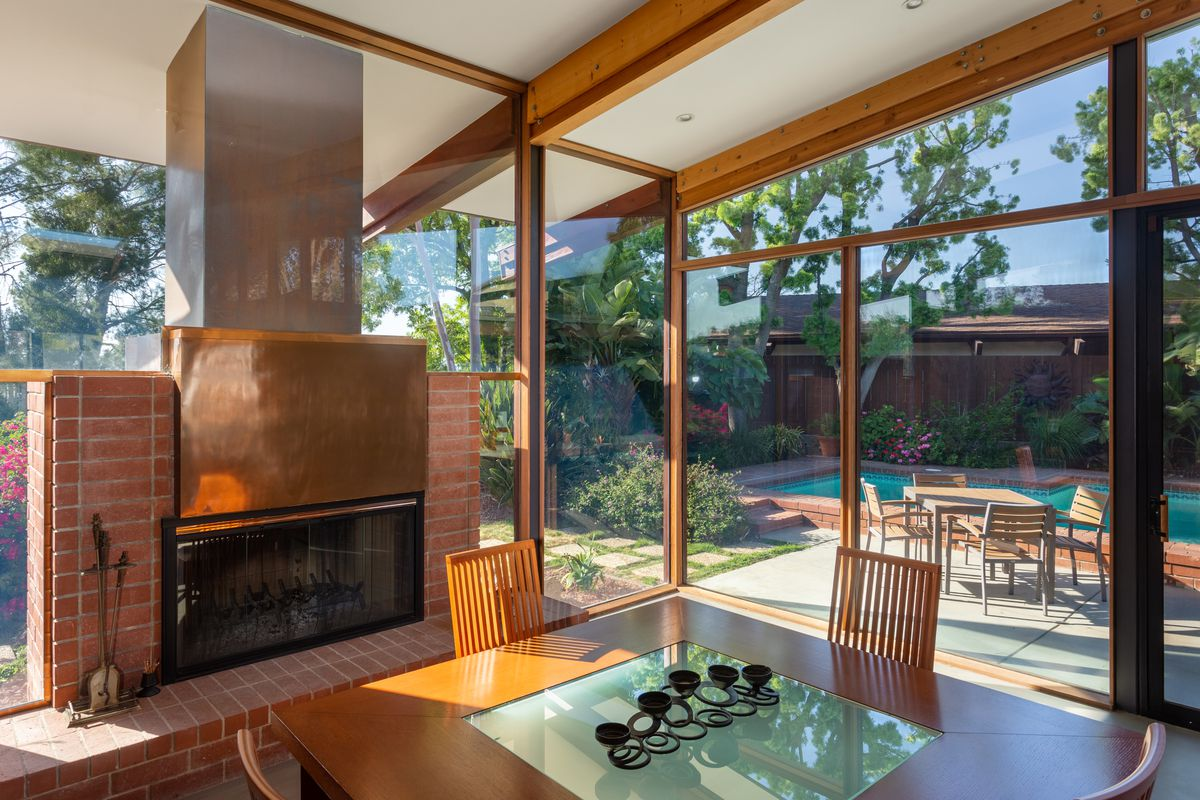 A brick fireplace surrounded by glass walls.