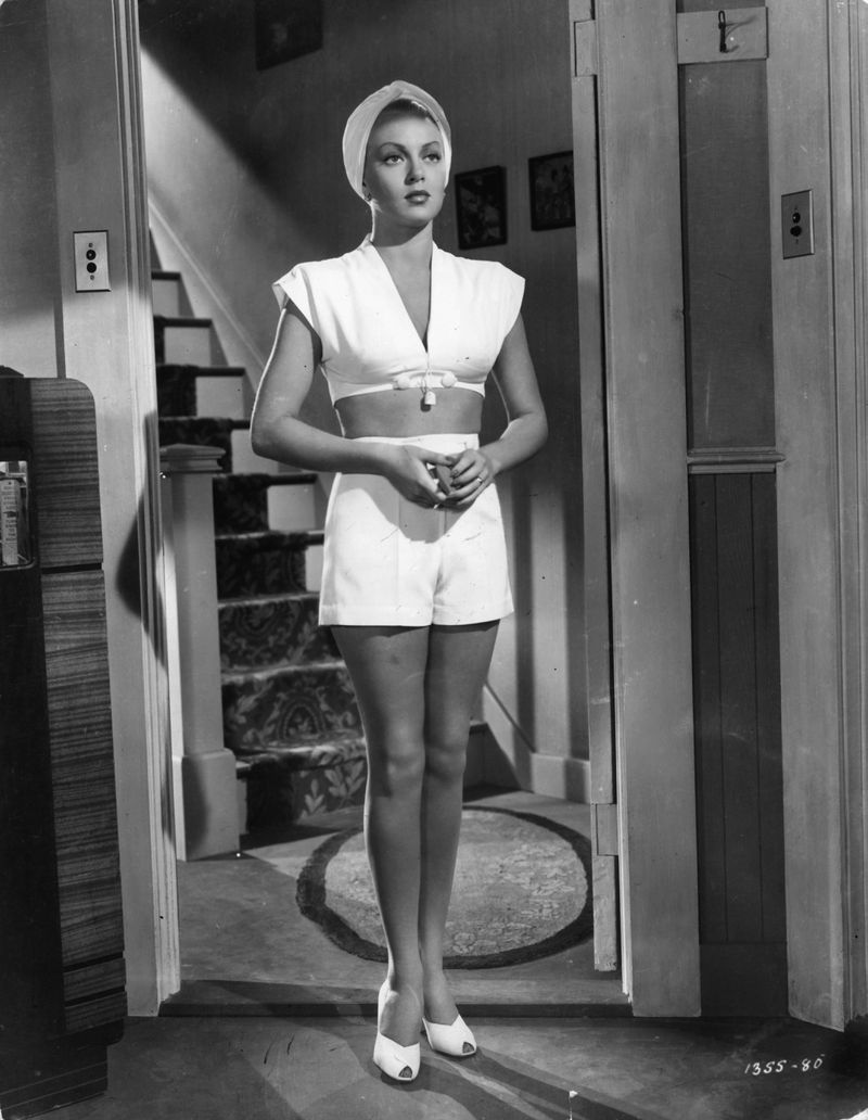 A black and white image of a statuesque Lana Turner standing in a doorway, dressed in high-rise, pleated shorts, white crop top with a deep-V and bow, and a turban.