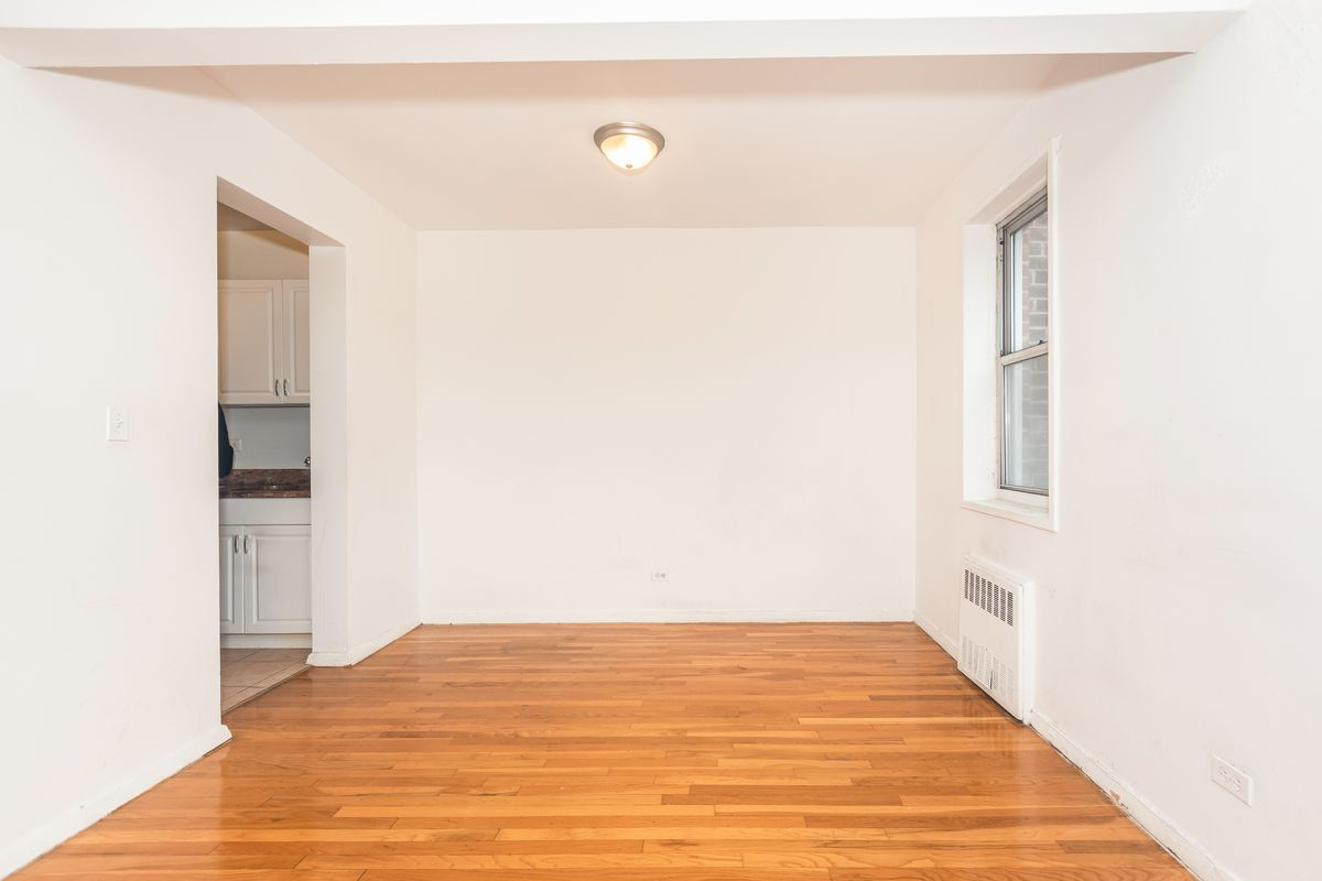 A living area with white walls, hardwood floors, and a window.
