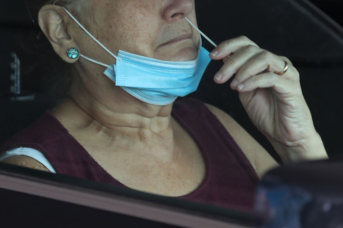 MIAMI, FLORIDA - JULY 23: A person uses a nasal swab for a self administered test at the new federally funded COVID-19 testing site at the Miami-Dade County Auditorium on July 23, 2020 in Miami, Florida. U.S. Surgeon Jerome M. Adams visited the site, as the state of Florida experiences a spike in coronavirus cases, to encourage people to wear a mask and take other precautions to fight the pandemic.