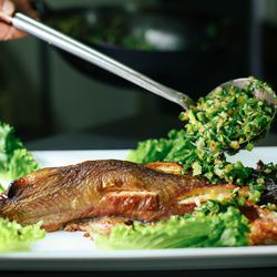 Fresh out of the oven, the catfish is garnished with a salad of green onions and garlic.