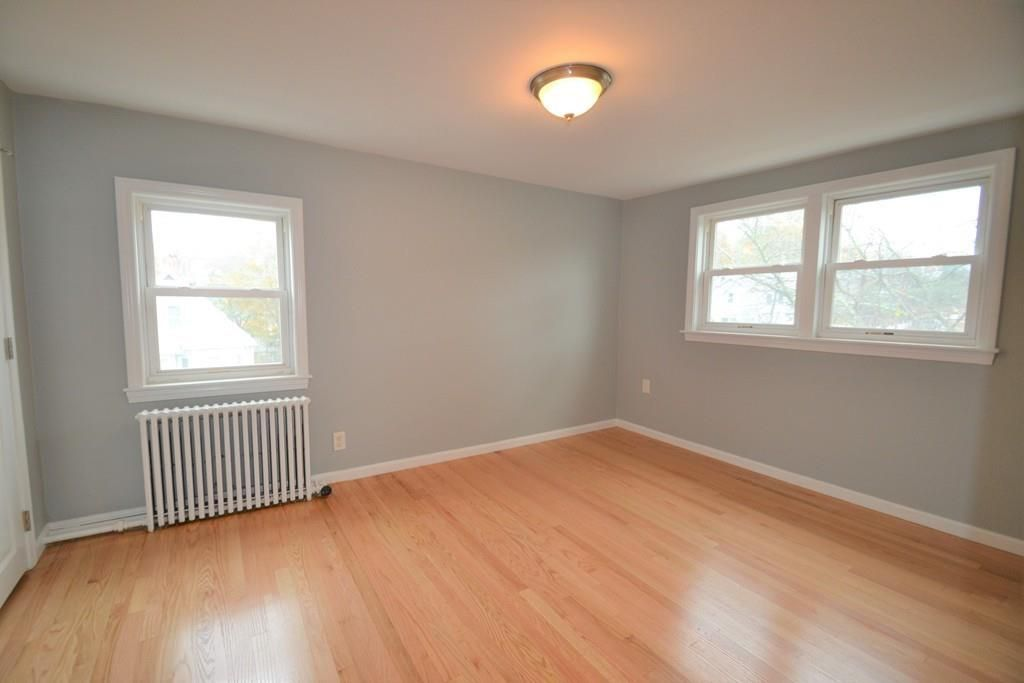 An empty bedroom with three windows and a radiator.