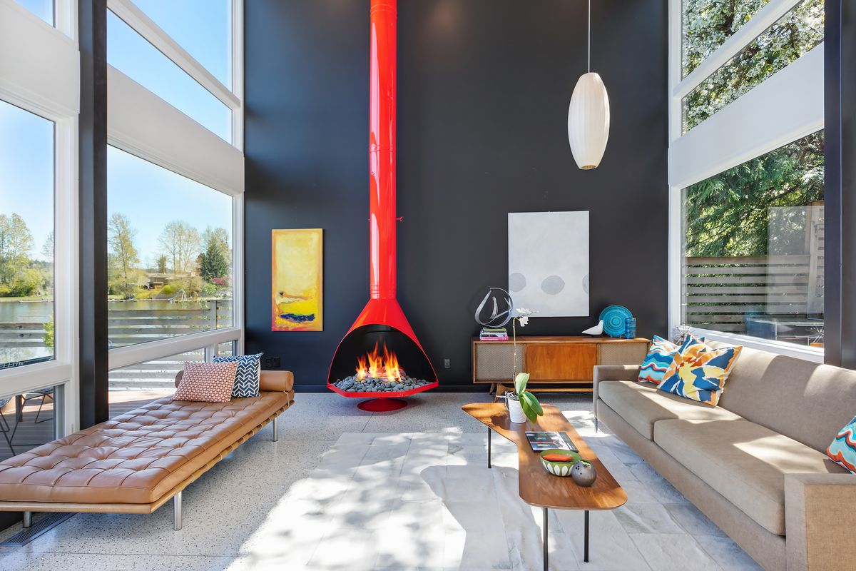 A double height living room with a bright orange fireplace, beige couch, and day bed.