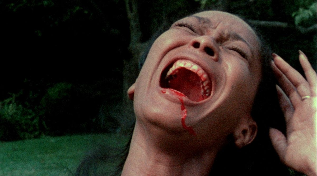 A Black woman with a bloody mouth screams in Ganja & Hess