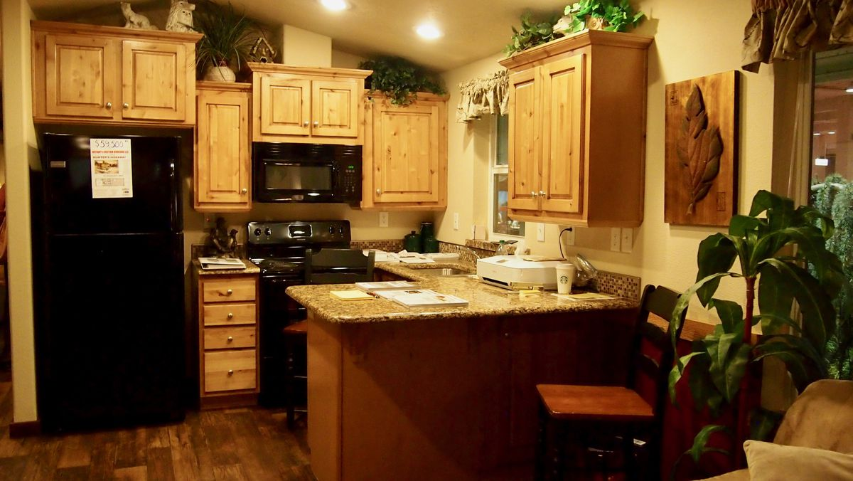 A small, open kitchen with lots of wood cabinets and black appliances.
