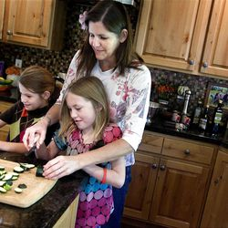 Cherise Udell, her daughter, Sophia, 7,left, and her friend, Shae Sorenson, 8, cut up vegetables for a pasta primavera salad that was to be donated to the OccupySLC demonstrators who are camped at Pioneer Park on Thursday, October 12, 2011.