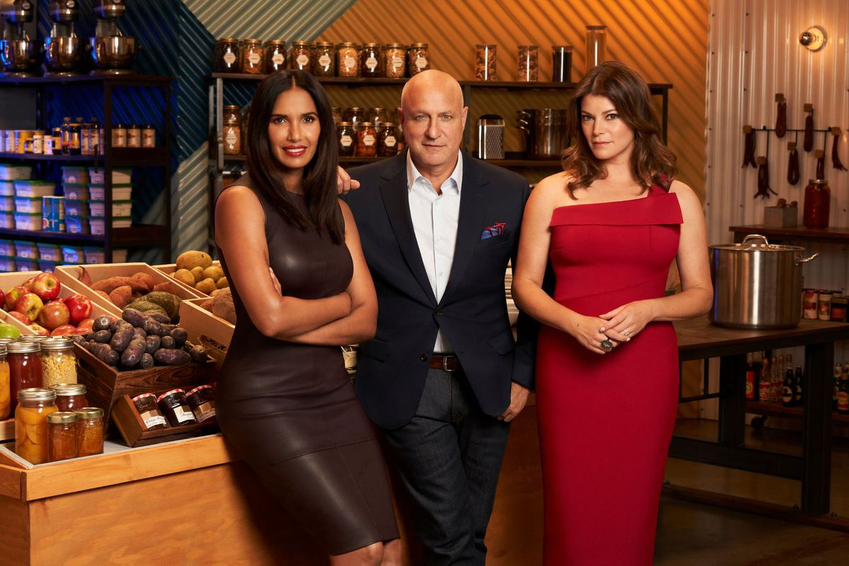 Padma Lakshmi, Tom Colicchio, and Gail Simmons stand in the grocery store set of Top Chef