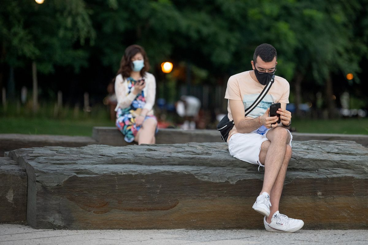 Two people sitting well apart in a park, each looking at their phone.