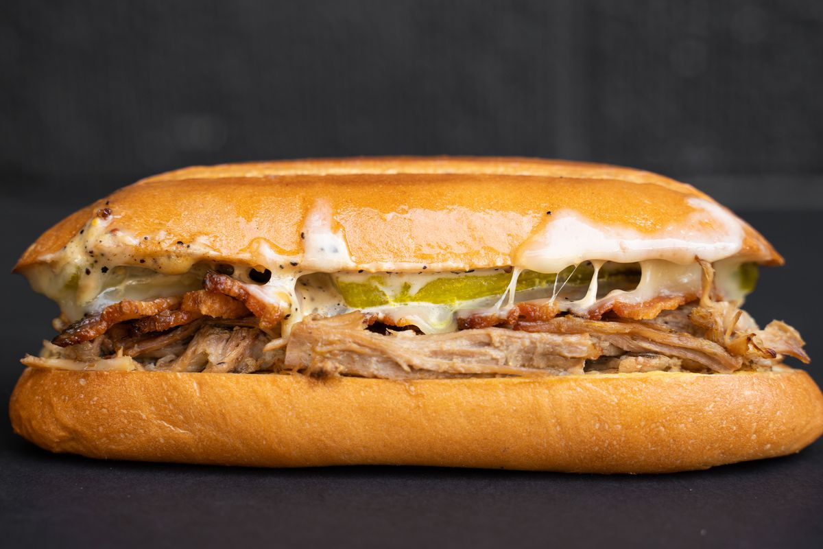 A close-up shot of a horizontal sandwich dripping with cheese and roasted pork.