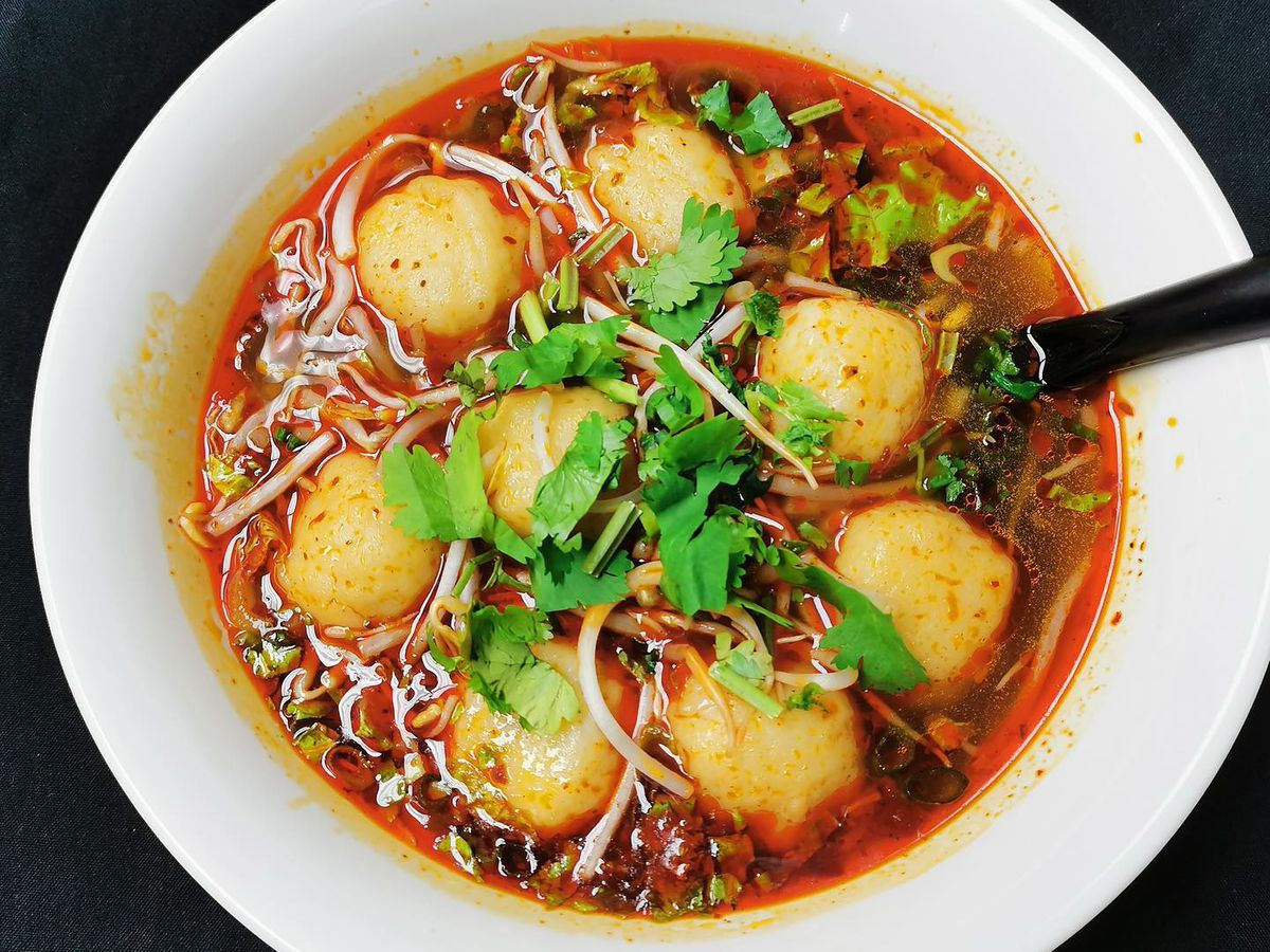 Spicy fish soup dumplings in red broth with herbs in a white bowl