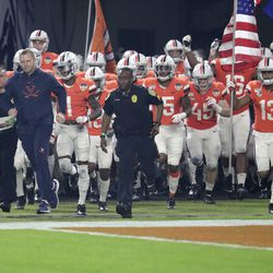 Virginia head coach Bronco Mendenhall, left, runs onto the field as wide receiver Terrell Jana (13) carries the American flag during the first half of the Orange Bowl NCAA college football game against Florida, Monday, Dec. 30, 2019, in Miami Gardens, Fla.
