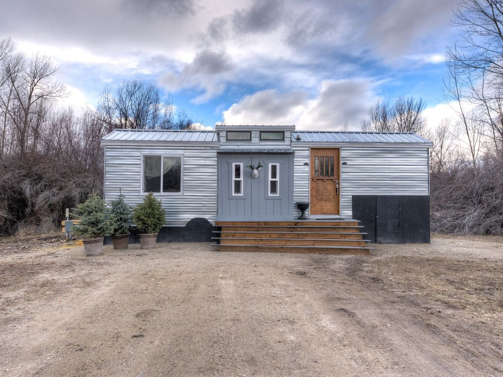 The exterior of a tiny home in Montana. There is a wooden door and stairs. The facade is metallic.