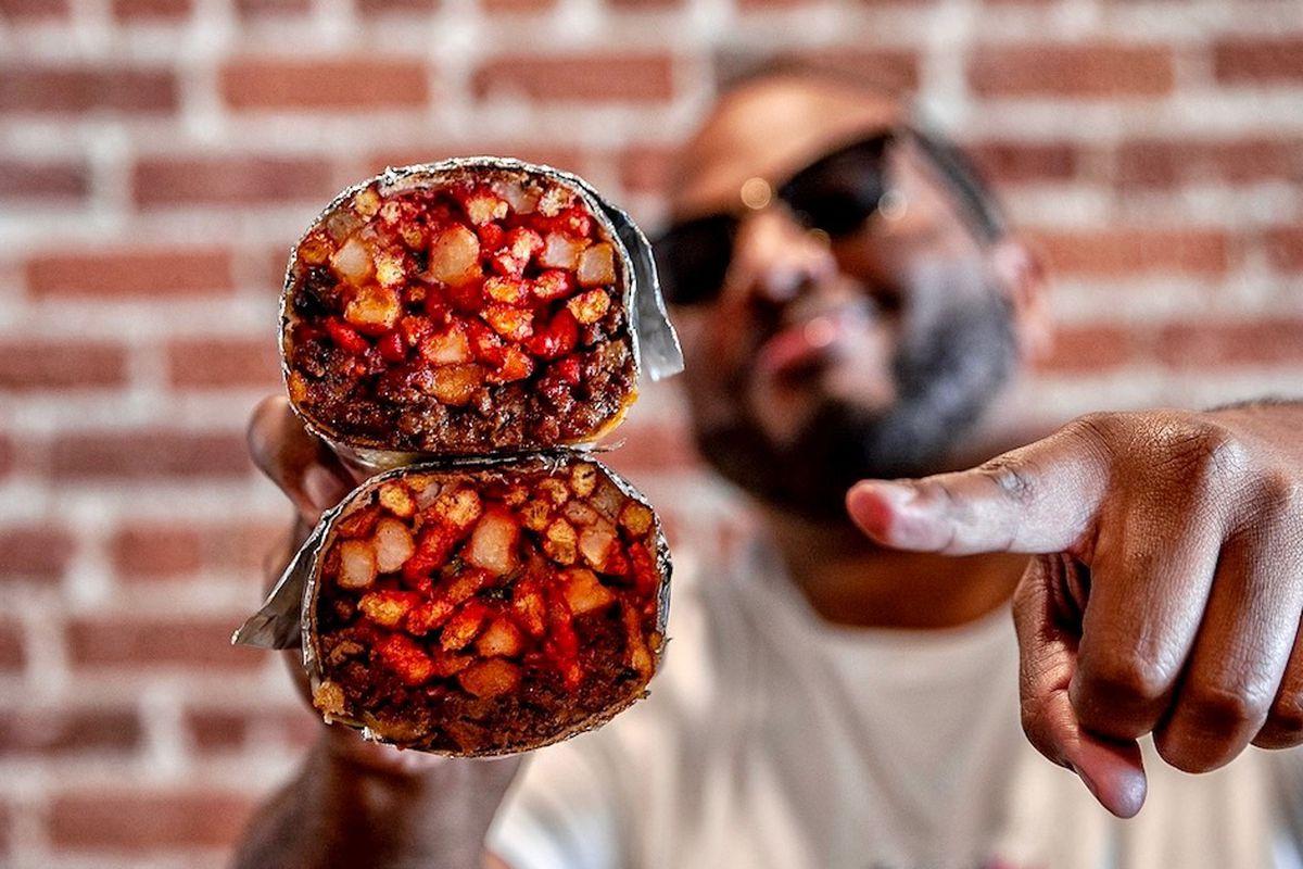 A man holds a big red burrito cut in half