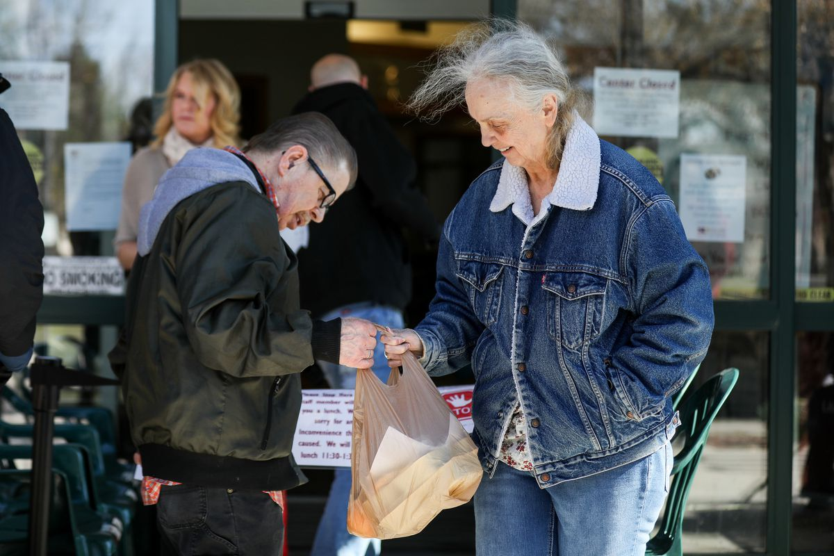 Doug Ruff and Dorothy Paraspoll collect a couple of packed lunches at the Liberty Senior Center in Salt Lake City on Tuesday, March 17, 2020. Senior centers are not allowing people to congregate for meals due to concerns over spreading COVID-19 but are instead letting seniors pick up their meals.